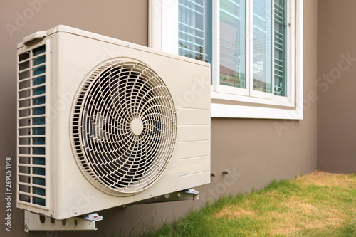 Photo Air conditioner compressor outdoor unit installed outside the house