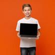 Leinwandbild Motiv Happy smiling boy showing blank laptop computer