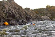 Man In Blue Kayak On Whitewater On Fast Mountain River Among The Rapids At Dusk. Whitewater Kayaking, Extreme Water Sport. Kayak Freestyle