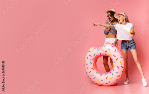 Foto  Emotional females pointing at empty space, standing with inflatable ring o