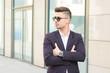 Portrait of successful businessman open in modern city near business center