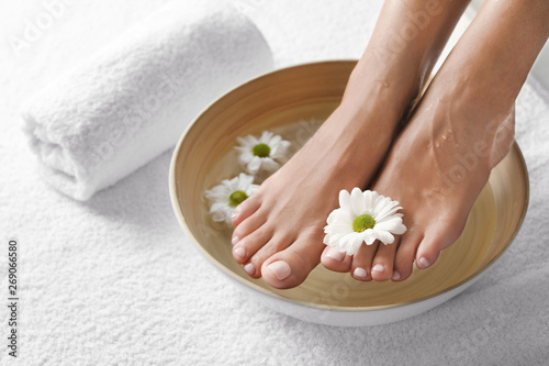 Closeup view of woman soaking her feet in dish with water and flowers on white towel, space for text. Spa treatment