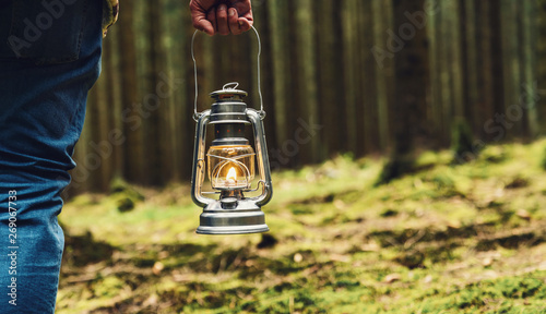 hiker holding a Old oil lamp in the forest Wallpaper Mural
