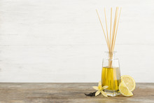 Aromatic Reed Freshener, Lemon And Vanilla On Wooden Table Against Light Background. Space For Text