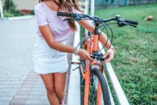Woman Summer City Bicycle Parking. Blocks Metal Cable Bicycle. Protection Property From Theft. Concept Anti-theft Lock With Cipher, Password Selection With Code Locks Cable With Numeric Code Lock.