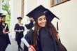 Leinwandbild Motiv Female graduates with diplomas in their hands hugging