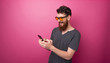 canvas print picture - Photo pf stylish bearded man using a mobile phone, pink isolated background
