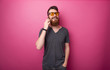 Portrait of handsome  bearded man talking on phone with firends over isolated pink background