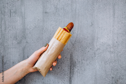Fotografia French hot dog in a bacon with fried sausage in a woman's hand against the wall