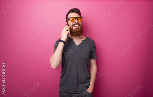 Fotografía  Portrait of handsome  bearded man talking on phone with firends over isolated pi
