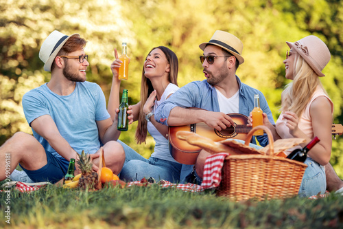 Magasin de musique Group of friends on picnic with guitar