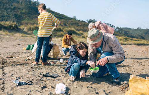 Fototapeta  Group of volunteers picking up trash on the beach