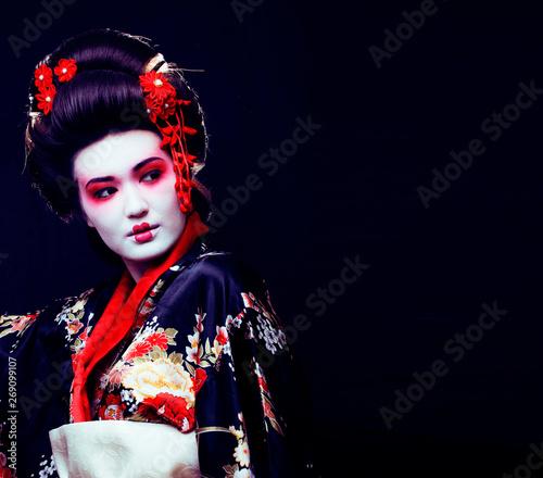 Fotografía young pretty real geisha in kimono with sakura and decoration on black backgroun