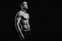 Muscular Model Young Man On Dark Background. Black And White Fashion Portrait Of Strong Brutal Guy With Modern Trendy Hairstyle. Sexy Naked Torso Six Pack Abs. Male Flexing His Muscles. Sport Concept.