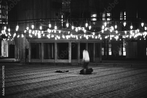 Valokuva  Muslim believer praying inside a mosque, black and white photo, grain film added