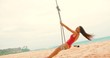 Attractive young woman on the shores of the Indian Ocean rides on a swing tied to the top of a palm tree. in slow motion