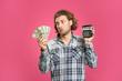 Leinwandbild Motiv Confused man with money and calculator on color background