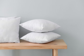 Fototapeta na wymiar Soft pillows on table against light wall