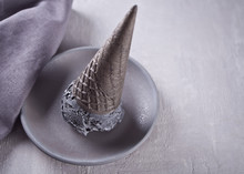 Black Ice Cream In Traditional Portioned Ice Cream Cones. On A White Ceramic Plate, On A Gray Table With Black Mug And Gray Napkin.