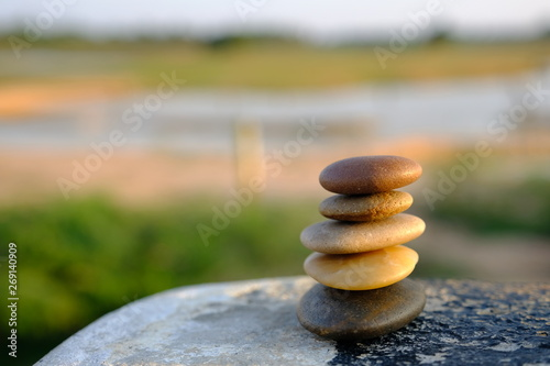 Foto op Aluminium Stenen in het Zand stack of stones on background of blue sky and water