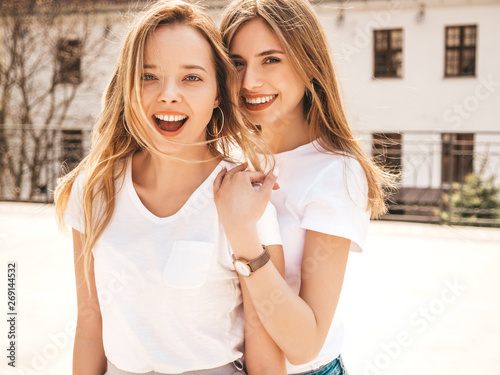 Pinturas sobre lienzo  Portrait of two young beautiful blond smiling hipster girls in trendy summer white t-shirt clothes