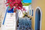Fototapeta Uliczki - Scenic alley with beautiful pink bougainvillea flowers and yellow house walls. Colourful Greek street in Lefkes, Paros island