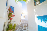 Fototapeta Uliczki - Street with beautiful pink bougainvillea flowers and white house walls. Colourful Greek street in Lefkes, Paros island