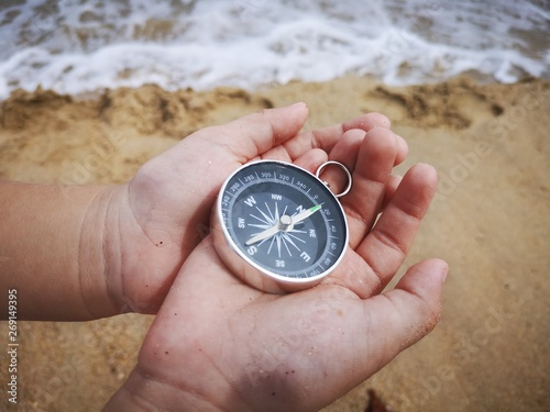 Photo  A little boy holding a compass is an instrument used for navigation and orientation that shows direction relative to the geographic cardinal directions