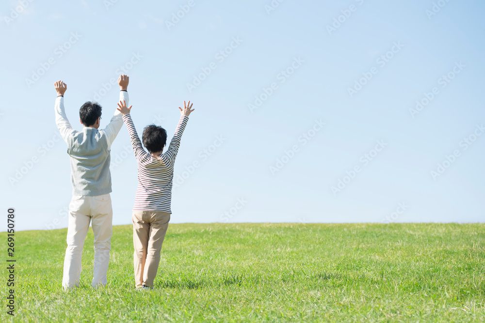 Fototapeta 草原で両手を挙げるシニア夫婦の後姿
