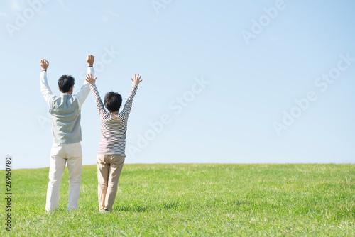 Fotografia 草原で両手を挙げるシニア夫婦の後姿