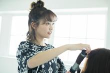 女性の髪の毛をスタイリングする女性美容師