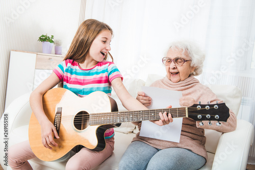 Fototapeta Smiling grandmother with granddaughter singing together with guitar