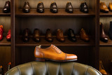 Fototapeta Uliczki - Brown full grain leather shoe in front of wooden display in men shoes boutique store.
