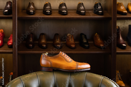 Brown full grain leather shoe in front of wooden display in men shoes boutique store. © Sergey Peterman