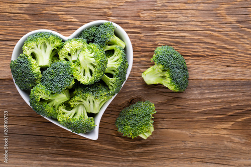 Photo  Fresh broccoli in a heart shaped bowl on a wooden background.