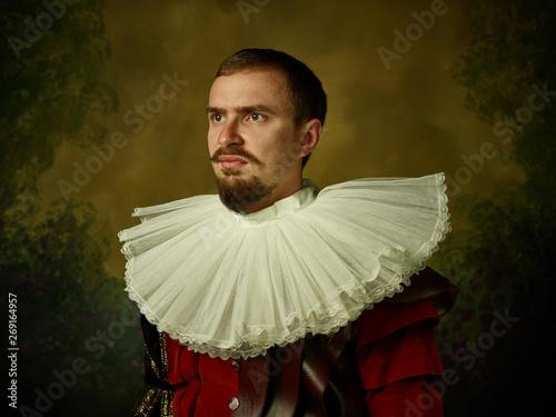 Obraz na plátně Young man as a medieval knight on dark studio background