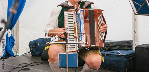 An accordionist in traditional Bavarian clothes plays the accordion on the stage Wallpaper Mural