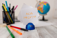 Text Sign Showing Non Profit. Business Photo Showcasing Not Making Or Conducted Primarily To Make Profit Organization Stationary Plus Pens And Papers With Artificial Globe On The Wooden Desk