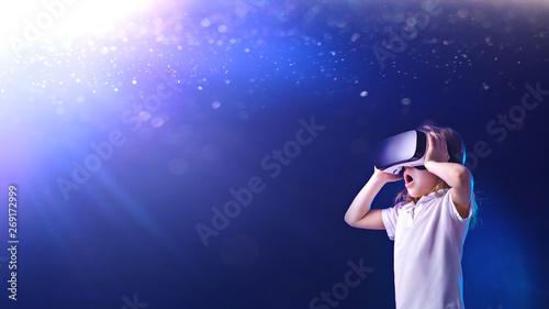 Fotografie, Tablou  Surprised female kid using digital glasses of virtual reality on shining blue ba