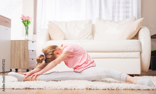 Motivated child doing hard stretches at home, in the living room Canvas Print