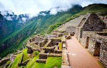 Sunshine Breathtaking View Of Machupicchu Stone Anchient Walls And Temple Among Mountains Covered With Clouds