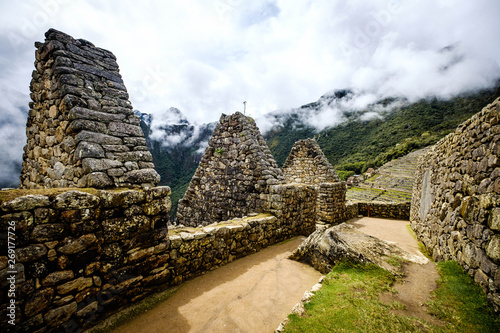 Tuinposter Hoogte schaal Sunshine breathtaking view of Machupicchu stone anchient walls and temple among mountains covered with clouds