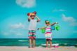 Leinwandbild Motiv happy girl and boy play with toys on beach