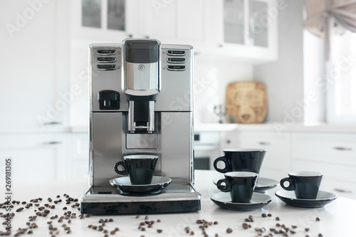 Photo Coffee machine with cups for espresso on the kitchen table
