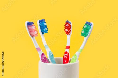 Fotografiet Cepillos de dientes vista de frente sobre fondo amarillo