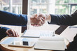 Finishing up a meeting, handshake of two happy business people after contract agreement to become a partner, collaborative teamwork