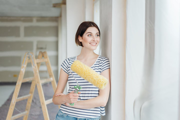 Woman admiring the newly painted wall in her house