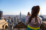 Fototapeta Nowy Jork - Tourist taking picture of New York City cityscape. Young woman looking at Manhattan panorama