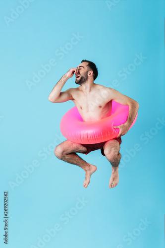 Photo of masculine shirtless tourist man wearing rubber ring smiling while swimm Tapéta, Fotótapéta