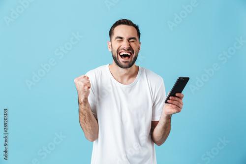 Fotografía  Photo of emotional brunette man wearing basic t-shirt laughing and holding smart